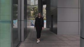 Una mujer europea joven camina a través de un arco del edificio moderno del negocio en centro de la ciudad almacen de video