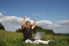 Una mujer exulting con una computadora portátil Fotografía de archivo