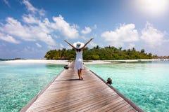 Una mujer feliz camina abajo de un embarcadero de madera en los Maldivas Imagen de archivo