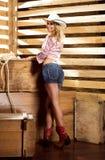 Una mujer feliz del vaquero en ropa atractiva en un granero Fotos de archivo libres de regalías