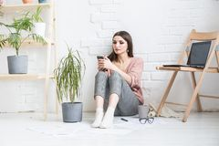 Una mujer feliz en ropa casual hecha en casa se sienta en un interior brillante y utiliza un tel?fono, la muchacha est? descansan fotografía de archivo libre de regalías