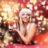 Una mujer feliz en un sombrero de la Navidad con un presente Fotos de archivo libres de regalías