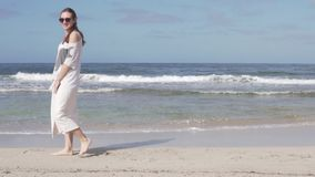 Una mujer feliz está caminando lentamente en una playa arenosa a lo largo del mar almacen de video