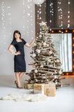 Una mujer feliz joven adorna un árbol de navidad para la Navidad Conce Imagen de archivo libre de regalías