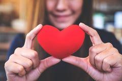 Una mujer feliz que lleva a cabo una muestra roja del corazón con la sensación en amor Imagen de archivo libre de regalías