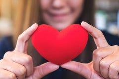 Una mujer feliz que lleva a cabo una muestra roja del corazón con la sensación en amor Fotografía de archivo