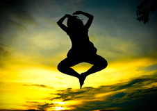 Una mujer feliz que salta en la puesta del sol fotografía de archivo