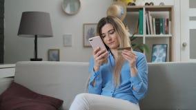 Una mujer feliz y sonriente que hace un pago de la tarjeta con smartphone a los proyectos ley de remuneración Una muchacha atract almacen de video