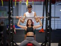 Una mujer fuerte con el cuerpo atlético hermoso que hace ejercicios con un barbell en un fondo del gimnasio Concepto del levantam imagen de archivo
