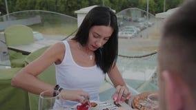 Una mujer goza el comer de las alas de pollo frito en un restaurante en la terraza abierta almacen de metraje de vídeo