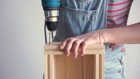Una mujer hace un trabajo no-femenino - perfora un agujero con un destornillador en una caja de madera, cámara lenta metrajes