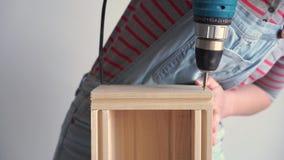 Una mujer hace un trabajo no-femenino - perfora un agujero con un destornillador en una caja de madera, c?mara lenta almacen de video