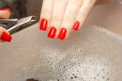 Una mujer hace una manicura con una herramienta Clavos rojos empapados en un baño con agua Imágenes de archivo libres de regalías