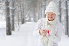 Una mujer hermosa comienza a abrir el regalo Imágenes de archivo libres de regalías