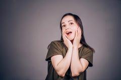 Una mujer hermosa con una boca abierta y una sorpresa mira para arriba, las noticias inesperadas recibidas o los regalos Alegría, imagen de archivo libre de regalías