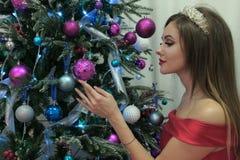 Una mujer hermosa cuelga para arriba los juguetes en un árbol del nuevo-año en un vestido rojo Tema de la Feliz Año Nuevo y de la foto de archivo