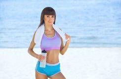 Una mujer hermosa de los deportes sostiene una botella de agua en sus manos, en sus mentiras del hombro una toalla blanca Imágenes de archivo libres de regalías
