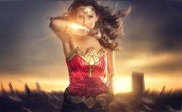 Una mujer hermosa del super héroe que corre en la puesta del sol imagenes de archivo