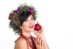 Una mujer hermosa en una guirnalda de las ramas de árbol de navidad y nuevo Fotografía de archivo libre de regalías