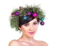 Una mujer hermosa en una guirnalda de las ramas de árbol de navidad y nuevo Foto de archivo