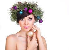 Una mujer hermosa en una guirnalda de las ramas de árbol de navidad y nuevo Imagen de archivo