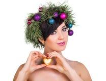 Una mujer hermosa en una guirnalda de las ramas de árbol de navidad y nuevo Imágenes de archivo libres de regalías