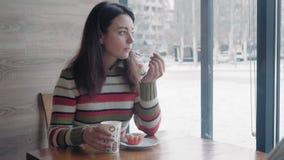 Una mujer hermosa en un suéter caliente que come la torta y que bebe el café que se sienta en un café y que mira el nevado almacen de metraje de vídeo