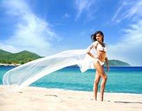 Una mujer hermosa en un traje de baño que presenta en la playa Imagen de archivo