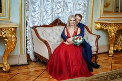 Una mujer hermosa en un vestido rojo con un hombre que se sienta en una silla, la novia y el novio, recienes casados felices fotos de archivo libres de regalías