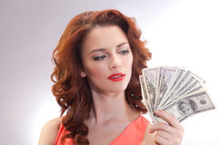 Una mujer hermosa en un vestido rosado con los billetes de banco del dólar en las manos foto de archivo