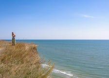 Una mujer hermosa en un vestido verde está sobre la alta playa imagen de archivo