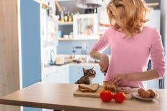Una mujer hermosa está cocinando el desayuno mientras que su gato que mira la y la comida de la espera Imágenes de archivo libres de regalías