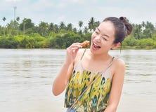 Una mujer hermosa est? comiendo feliz el pollo imagen de archivo libre de regalías