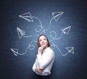 Una mujer hermosa está reflexionando sobre soluciones posibles del problema complicado Muchas flechas con diversas direcciones so Imagen de archivo