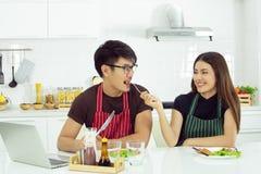 Una mujer hermosa está tomando cuidado de su novio hermoso en la cocina imagen de archivo libre de regalías