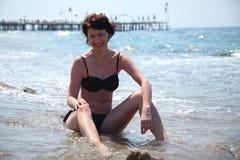 Una mujer hermosa está tomando el sol en el sol en el mar Fotos de archivo