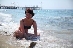 Una mujer hermosa está tomando el sol en el sol en el mar Imagen de archivo