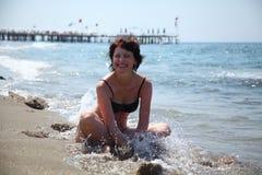 Una mujer hermosa está tomando el sol en el sol en el mar Imagenes de archivo