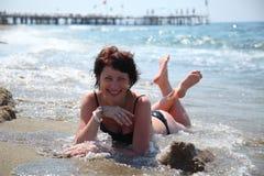 Una mujer hermosa está tomando el sol en el sol en el mar Fotografía de archivo libre de regalías