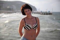 Una mujer hermosa está tomando el sol en el sol en el mar Foto de archivo libre de regalías