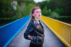 Una mujer hermosa joven con un brillo violeta en su cara que se coloca en el puente Imágenes de archivo libres de regalías