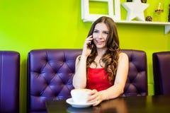 Una mujer hermosa joven está bebiendo el café en un café Fotografía de archivo libre de regalías