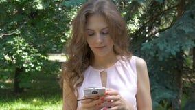 Una mujer hermosa joven está cogiendo SMS en un smartphone metrajes