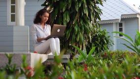 Una mujer hermosa joven se está sentando en el pórtico con un ordenador portátil almacen de video