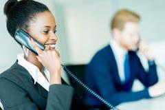 Una mujer hermosa, negra, joven que trabaja en un centro de atención telefónica en un o foto de archivo