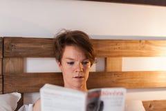 Una mujer hermosa que lee un libro en cama Fotos de archivo libres de regalías