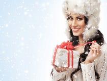 Una mujer hermosa que lleva a cabo un regalo de Navidad agradable Imagenes de archivo