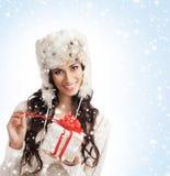 Una mujer hermosa que lleva a cabo un regalo de Navidad agradable Fotografía de archivo
