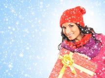 Una mujer hermosa que lleva a cabo un regalo de Navidad agradable Fotos de archivo libres de regalías