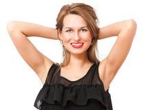 Una mujer hermosa que presenta y que sonríe coqueto Foto de archivo libre de regalías